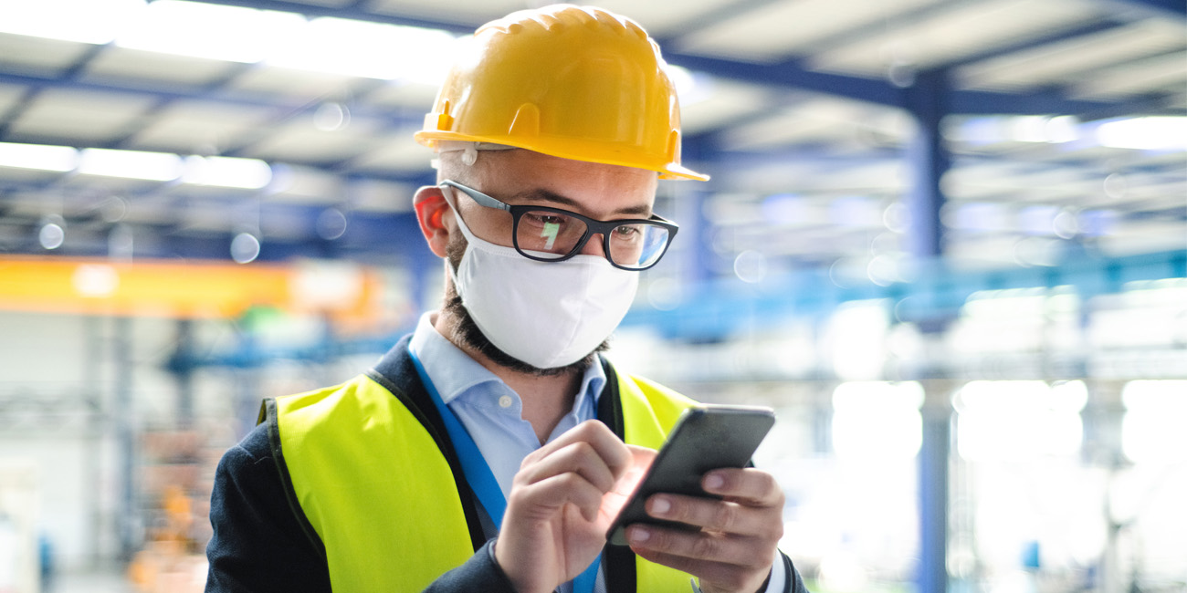 Technician wearing protective mask and hardhat checking his mobile device for an alert