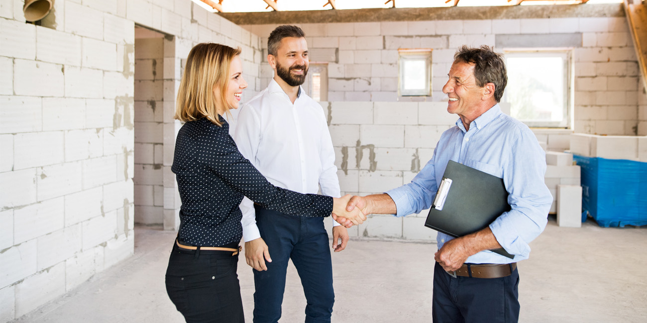Young businesswoman greets an older architect at a construction site.