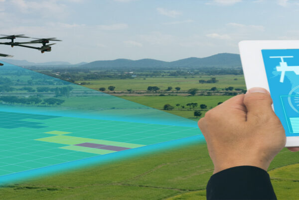 Drone hovering over a crop field collecting the data displayed on the iPad