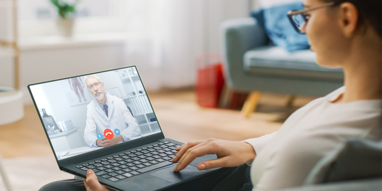 Young woman at home video chats with her physician on her laptop