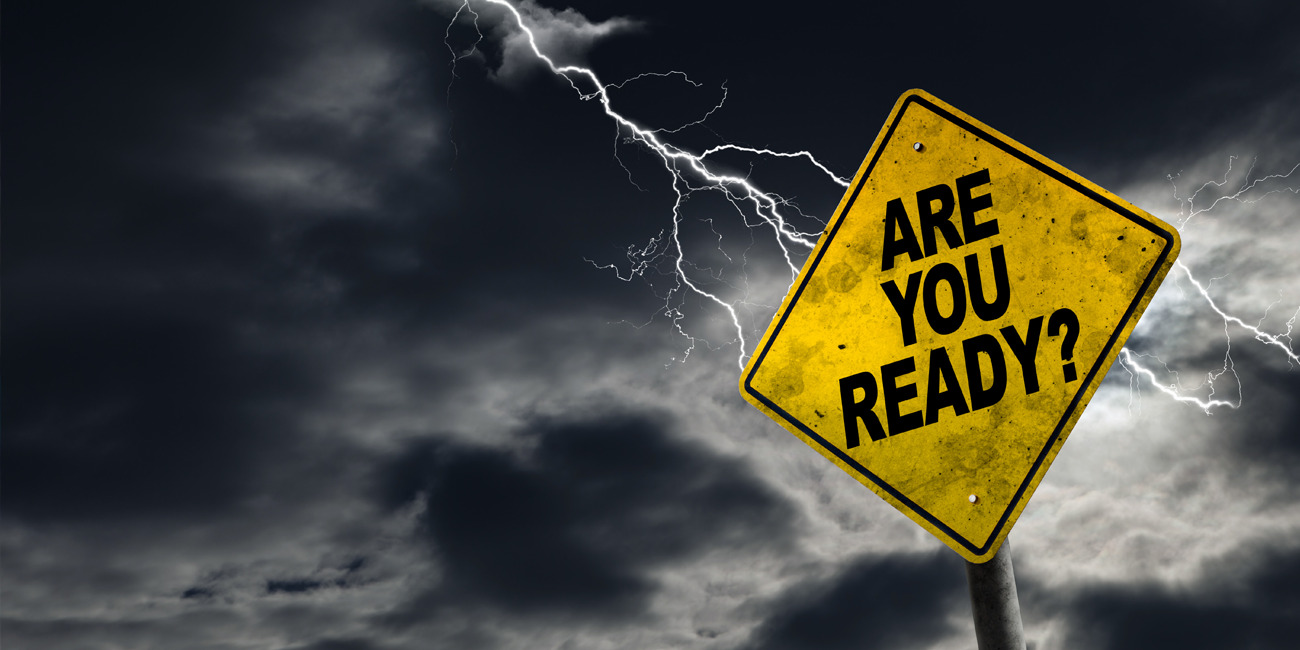 """Traffic sign with the words, """"Are you ready?"""" displayed, with dark clouds and a lightening strike in the background."""