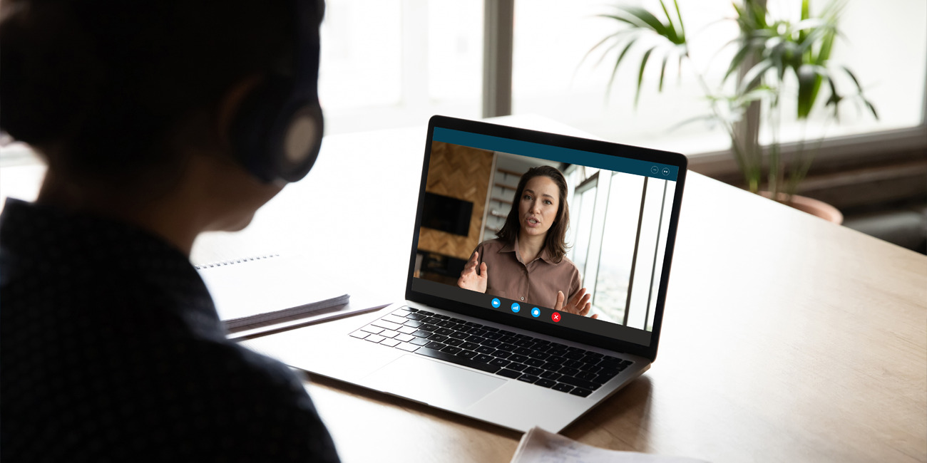 Employer on laptop screen conducting performance review while the employee listens and takes notes